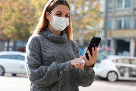 Beautiful woman with protective mask using mobile phone walking in city street