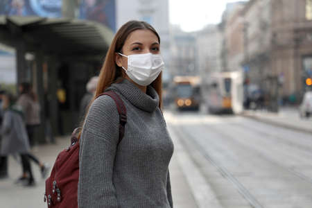 Student girl with protective mask waiting public transport in street. Young woman with surgical mask waiting tram at the stop in gray polluted city. Standard-Bild