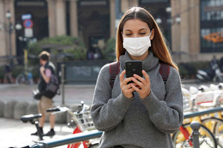 Young woman with protective mask using smartphone and looking on display in city center