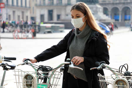 Eco-friendly transport. Business woman with protective mask taking a bicycle in a bike sharing platform. Young woman standing near bike sharing in the city. Standard-Bild