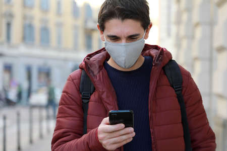 Young man with protective mask looks his smartphone while walking in street. Student guy with face mask using mobile phone outdoor.