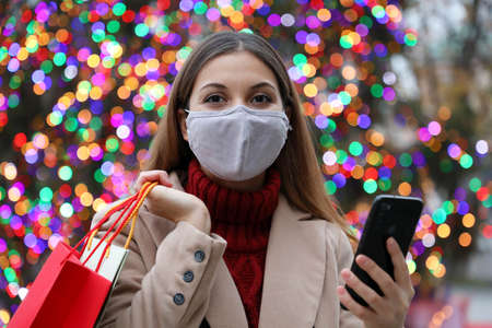 Beautiful fashion woman with face mask and shopping bags purchasing online with smart phone in the street with Christmas tree lights on the background looking at camera