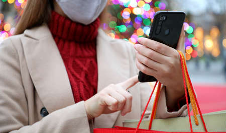 Young woman with protective mask using smartphone for shopping online and carrying bags on Christmas time. Cropped picture with focus on the hand and phone.