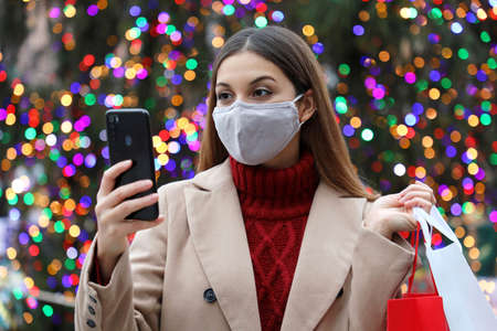 Christmas girl. Happy young woman with face mask carrying shopping bags in her hand buying christams presents with her smart phone outdoors.
