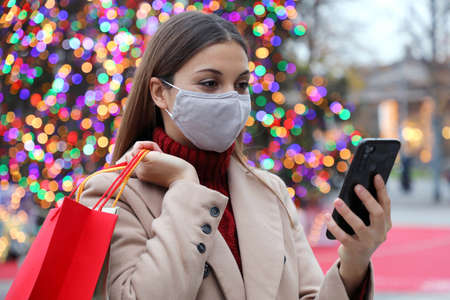Happy woman with face mask reading text on smartphone in Christmas time