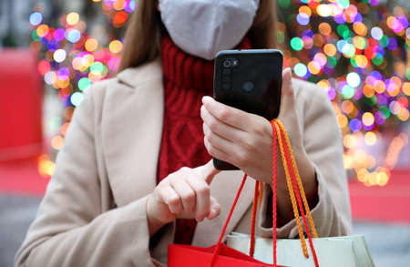 Unidentified woman with protective mask using mobile phone for shopping online and carrying bags on Christmas time. Focus on the hand. Standard-Bild