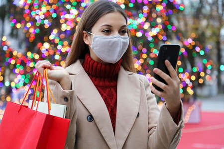 Young woman wearing face mask video calling with smartphone and shopping bags in the street on Christmas time