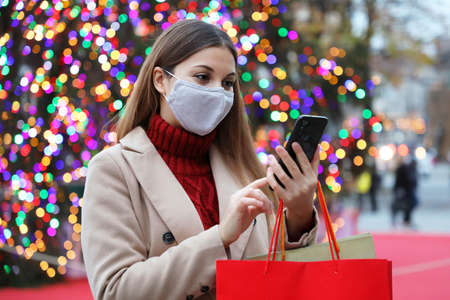 Christmas woman wearing face mask on street holding shopping bags and smart phone for online purchases with colorful christmas tree lights on background Standard-Bild