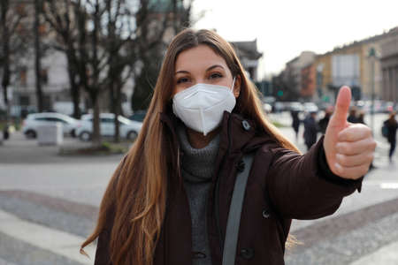 Optimistic young woman wearing protective mask FFP2 KN95 showing thumbs up in winter clothes outdoors.