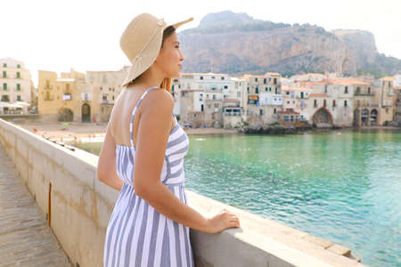 Young beautiful woman in a striped summer dress with hat enjoying view of Cefalu, seaside town, Sicily, Italy