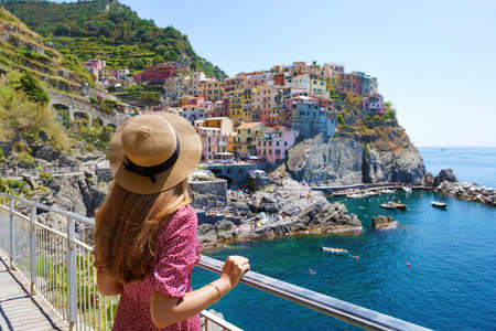 Young woman with hat and dress looking the amazing view of Manarola village in Cinque Terre, Italy. Archivio Fotografico