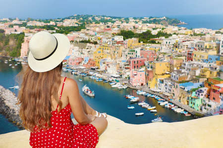 Beautiful young female tourist enjoying view of Marina di Corricella harbor and the village of Procida Island, Italy.