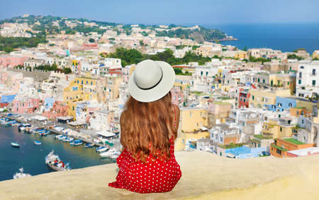 Travels in Italy. Back view of beautiful girl with hat sitting on wall looking at stunning panoramic view of Procida Island, Naples, Italy.