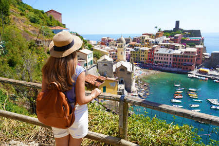 Summer holiday in Italy. Back view of young woman with backpack and hat looking at Vernazza village, Cinque Terre, Italy. Archivio Fotografico