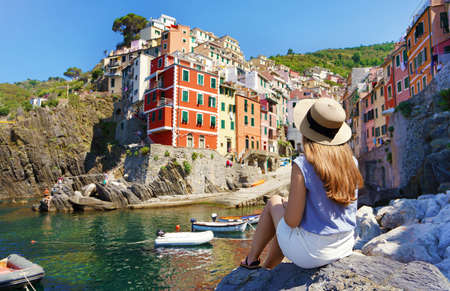 Tourism in Italy. Beautiful young woman sitting on stone enjoying stunning view of Riomaggiore colorful village, Cinque Terre, Italy. Archivio Fotografico