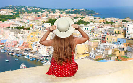 Beautiful young woman with hat sitting on wall looking at stunning panoramic view of Procida Island, Naples, Italy.