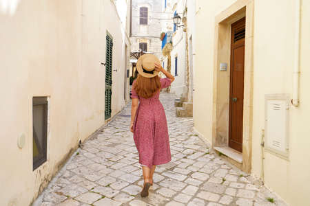 Back view of pretty tourist woman walking in narrow alley of typical old town of Italy