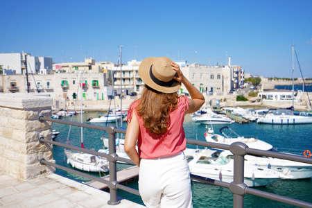 Stylish tourist girl walks along promenade of Giovinazzo picturesque harbor in Apulia, Italy