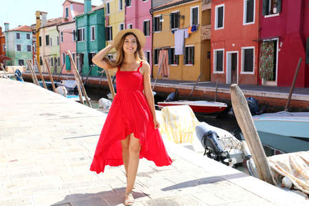 Full length of young beautiful dancer girl in Burano colorful town, Venice, Italy