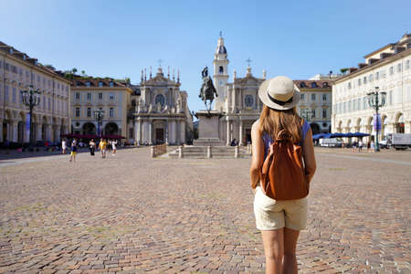 Tourism in Turin, Italy. Back view of traveler girl walking in San Carlo square enjoying cityscape of Turin, Italy. Young female backpacker visiting Europe.