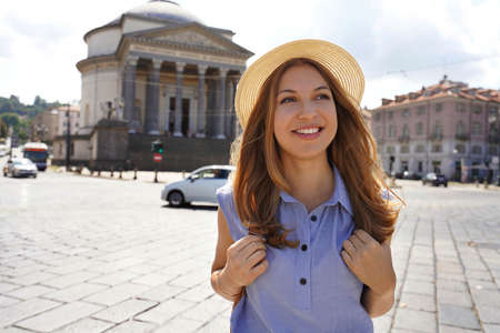 Attractive traveler girl walking in Turin with Gran Madre di Dio church on the background. Tourist girl walking in Turin, Italy.
