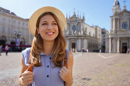 Portrait of beautiful tourist woman in Piazza San Carlo square in Turin, Italy. Traveler girl with Turin landmarks in Italy.