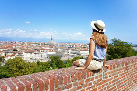 Beautiful young woman with hat sitting on wall looking at Turin cityscape, Italy