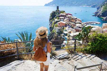Beautiful young traveler woman goes down the stairs and looking at stunning panoramic village of Vernazza on Cinque Terre, Italy