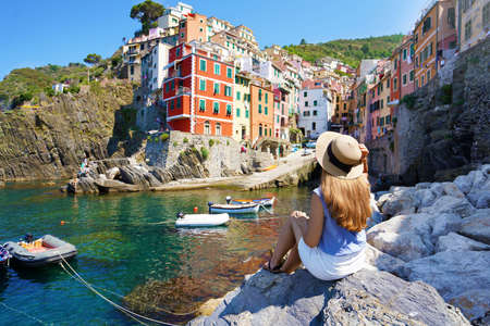 Holidays in Italy. Pretty young woman sitting on stone enjoying cityscape of Riomaggiore town with colorful houses, Cinque Terre, Italy.