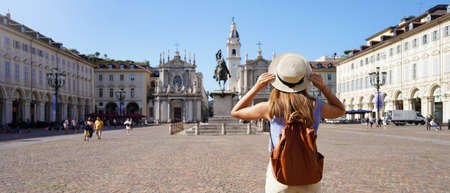 Holidays in Italy. Panoramic view of traveler girl walking in Piazza San Carlo square enjoying cityscape of Turin, Italy. Young female backpacker visiting Europe.