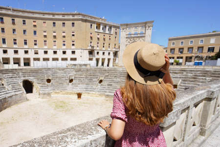 Tourism in Italy. Beautiful tourist girl visiting the Roman Amphitheater of Lecce, Italy.