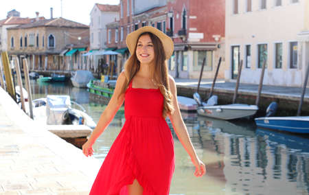 Romantic girl with red dress and hat walking alone between Murano old streets in Venice, Italy
