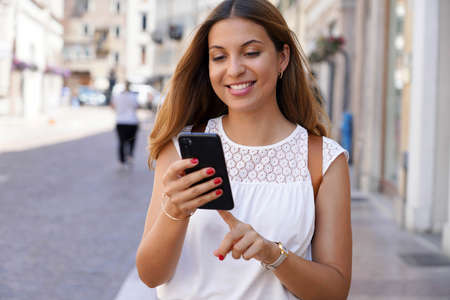 Brazilian dynamic girl using smartphone walking in street Archivio Fotografico
