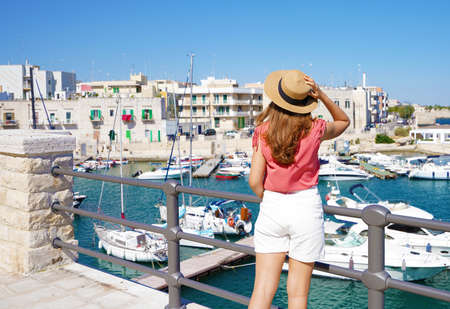 Holidays in Apulia. Back view of tourist girl wearing hat and looking at Giovinazzo picturesque harbor in Apulia, Italy.