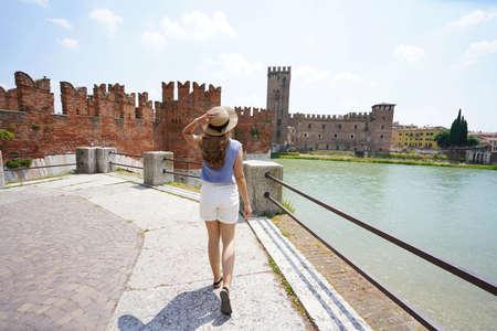 Promenade riverside in Verona, Italy. Beautiful lady walking along promenade with medieval and bridge on the background. Archivio Fotografico