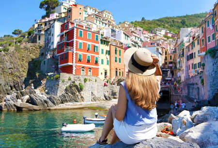 Beautiful young woman sitting on rock enjoying fantastic view of Riomaggiore colorful village in the Cinque Terre, Italy