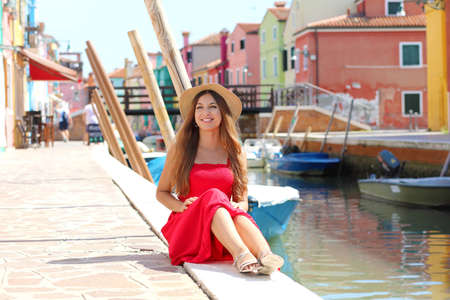 Attractive woman sitting on the edge of Venice channel in Burano village, Italy