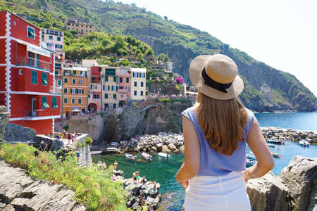 Enjoying vacation in Italy. Young traveling woman enjoying view of Riomaggiore village overhanging cliffs on sea.