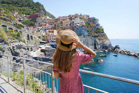 Young tourist woman enjoying traveling in Italy. Beautiful stylish girl with hat and dress looking at Manarola village overhanging the sea, Cinque Terre, Italy.