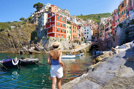 Vacation in Europe. Beautiful woman walking in Riomaggiore harbor looking at picturesque village overhanging cliffs, Cinque Terre, Italy.