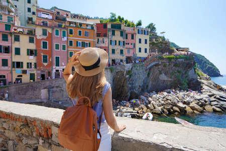 Young stylish woman looking at panoramic view of Riomaggiore colorful village, Cinque Terre, Italy Archivio Fotografico