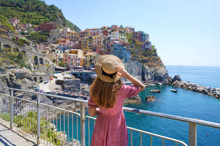Traveler girl enjoying vacations in Italy. Young woman wearing hat and dress looking at italian village of Manarola with sea. Archivio Fotografico