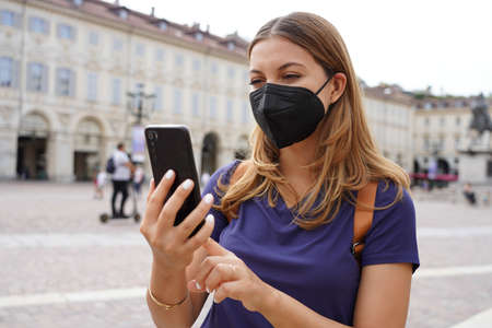 Portrait of young woman with black protective mask FFP2 KN95 using mobile phone with city background