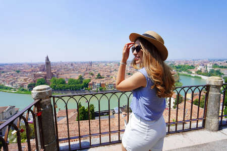 Glamor young woman with sunglasses and hat turns around on panoramic terrace in Verona, Italy