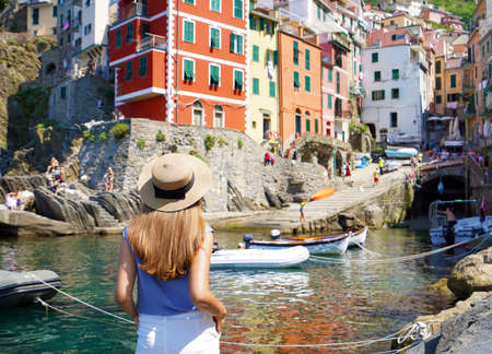 Holidays in Italy. Pretty young woman looking at the village of Riomaggiore from the harbor, Cinque Terre, Italy.