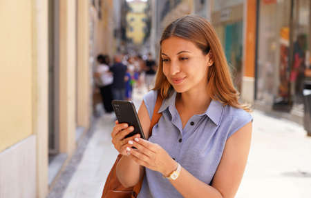 Happy young woman in city street using a mobile phone