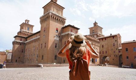 Travel in Italy. Back view of beautiful tourist girl enjoying view of Este (Castello Estense) of Ferrara, Italy.