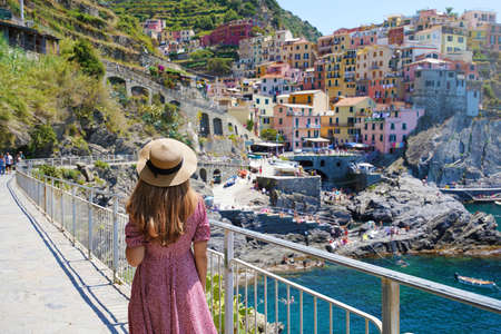 Beautiful young woman with hat and dress walking along the promenade of Manarola looking at stunning panoramic view of Manarola village in the Cinque Terre, Italy