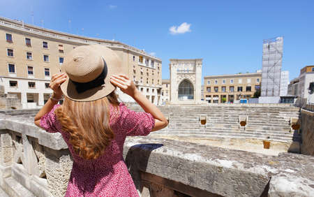 Cultural tourism in Italy. Beautiful tourist girl visiting ruins of Roman Amphitheater of the city of Lecce, Italy.