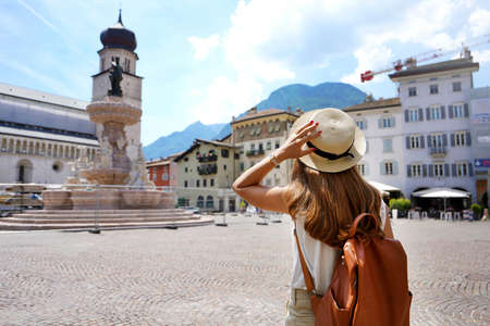 Cultural trip in Italy. Back view of traveler girl in the city of Trento, Italy.